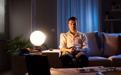 Hombre sentado en el sofá con una lámpara