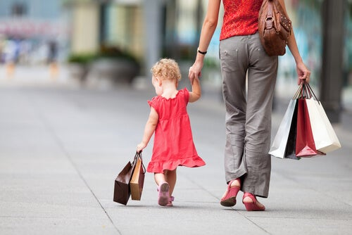 Madre e hija pequeña con bolsas de compras