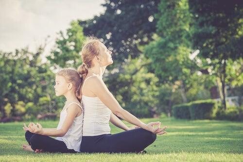 Madre e hija meditando dándose la espalda