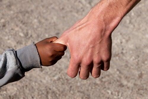 Mano de un niño sirio cogiendo la de un adulto
