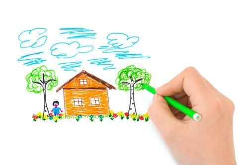 Mano dibujando una casa, un árbol y una persona