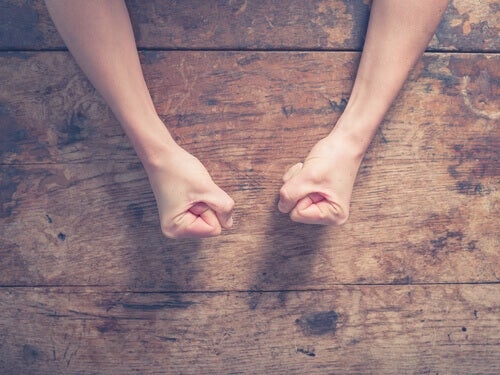 Manos cerradas de una persona enfadada encima de una mesa de madera