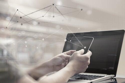 Manos de un hombre con móvil y al lado un ordenador