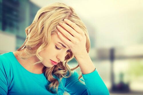 Mujer con la mano en la frente preocupada pensando en catástrofes
