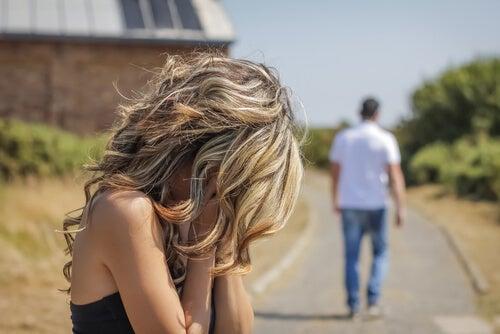 Mujer con las manos en la cara mientras su pareja se va