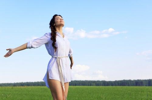 Mujer con los brazos abiertos vestida de blanco en el campo