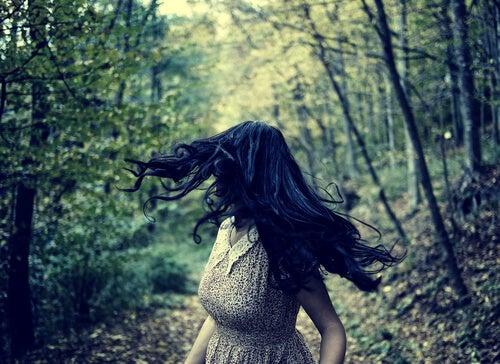 Mujer con miedo mirando hacia atrás en el camino