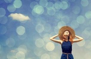 Mujer con sombrero mirando al cielo