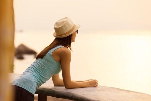 Mujer con un gorro mirando por el balcón