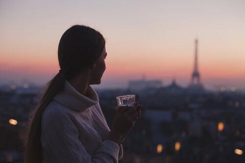 Mujer disfrutando de la vista de Paris con un vaso de café en la mano