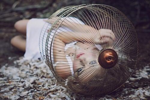 Mujer encerrada en una jaula tirada en el suelo