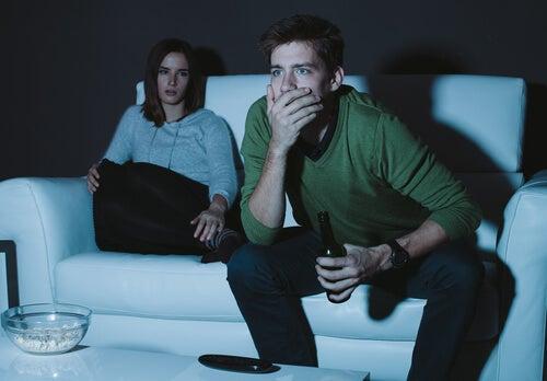 Mujer enfadada sentada en el sillón mientras su pareja ve el futbol
