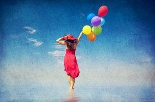 Mujer feliz caminando por el mar con globos de colores