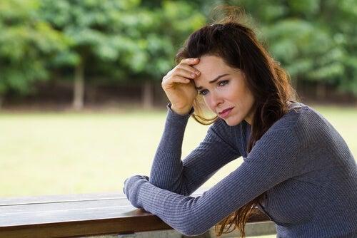Mujer preocupada y triste con la mano en la frente