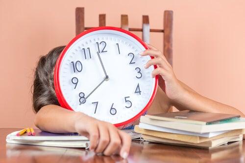 Niño con un reloj y muchos deberes
