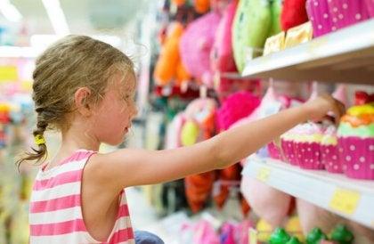 Niña cogiendo juguetes de una estantería