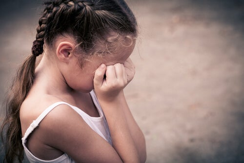 Niña con trenzas llorando con las manos en la cara