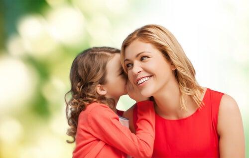 Niña contándole un secreto a su madre al oído