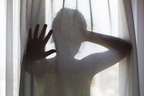 Niña detrás de una cortina