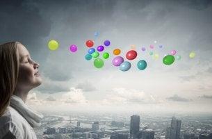 Niña imaginando globos de colores