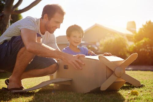 Niño montado en un avión de cartón jugando con su padre