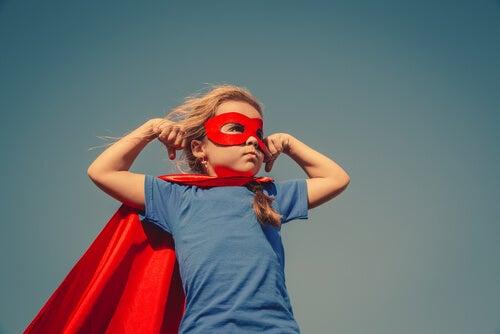 Niño vestido de superhéroe con una máscara y una capa rojas