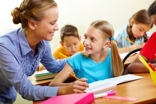 Profesora ayudando a su alumna en clase con las tareas
