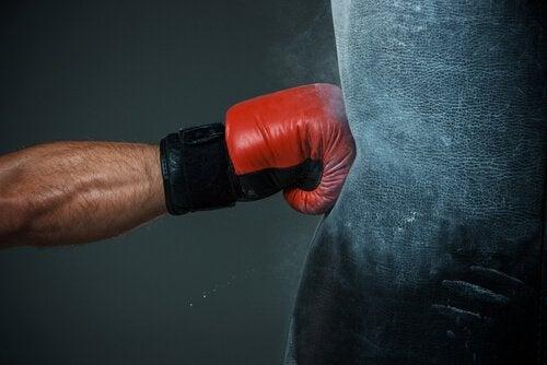 Brazo golpeando con rabia un saco de boxeo