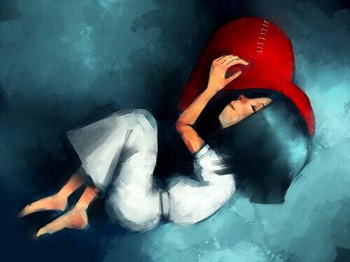 Chica durmiendo sobre un corazón en soledad