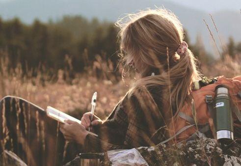 Mujer escribiendo en el campo
