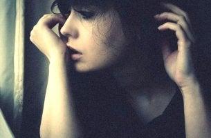 Chica mirando por la ventana con indiferencia