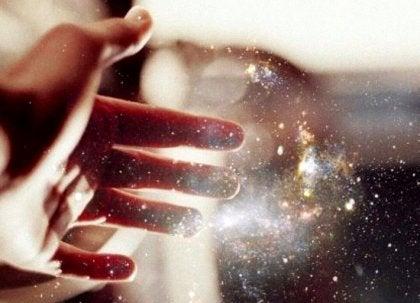 mano tocando un haz de energía