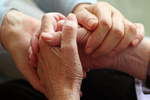 Cogiendo las manos de un moribundo simbolizando el arte de hacer el bien