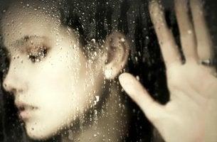 Mujer a través de un cristal simbolizando el dolor por la violencia sexual