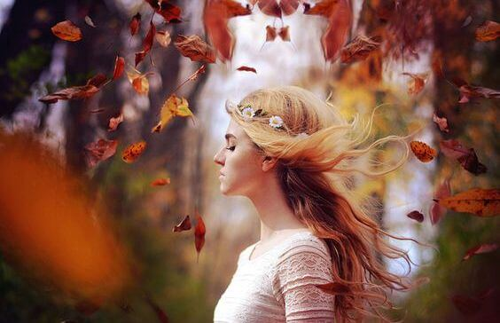 mujer con hojas alrededor sintiendo la intuición