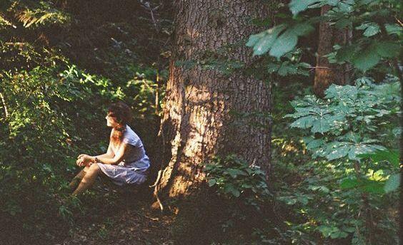 mujer sentada en el bosque pensando en su infelicidad