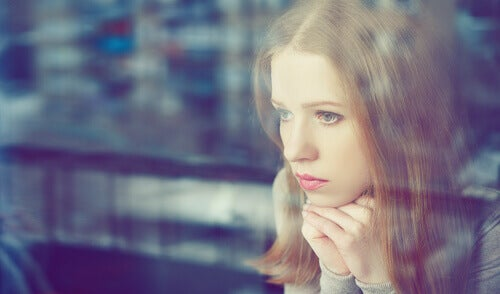 Mujer mirando por una ventana pensando en sus errores