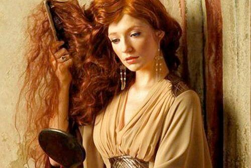 mujer pelirroja cepillándose el pelo