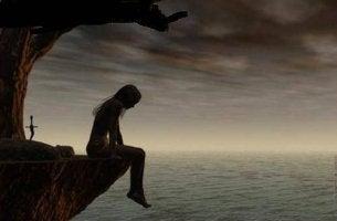 Mujer sentada en un precipio