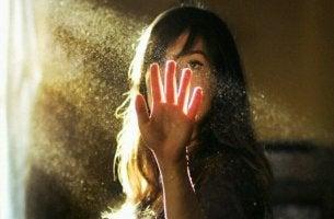 Mujer tocando un haz de luz por intuición