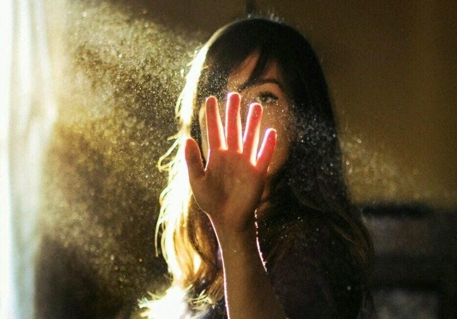 Mujer tocando un haz de luz