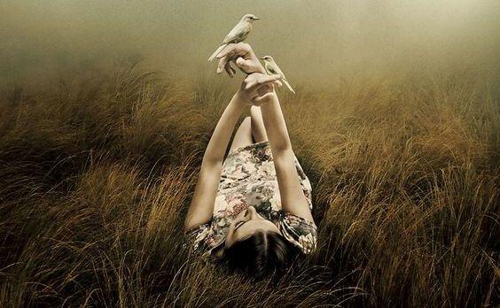 mujer tumbada con pájaros en las manos
