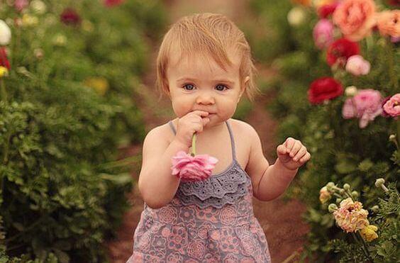 niña con flores disfrutando de los olores de infancia