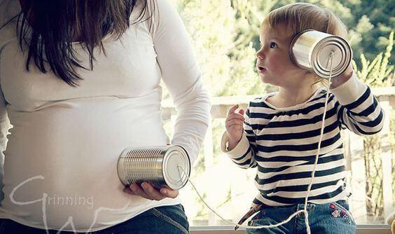 niño escuchando a su hermano en el embarazo de su madre