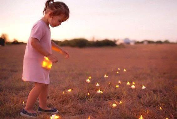 Niña recogiendo luces en el campo