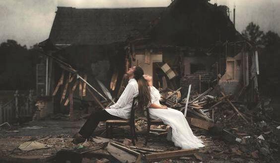 pareja ante una casa derruida