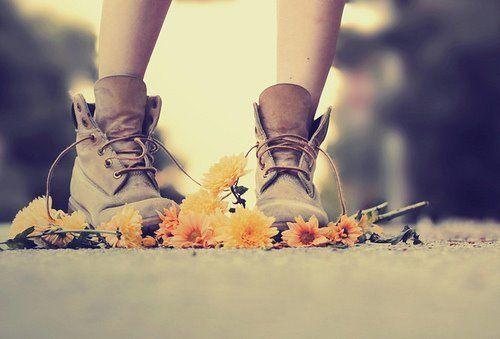 persona con botas ante margaritas en el suelo