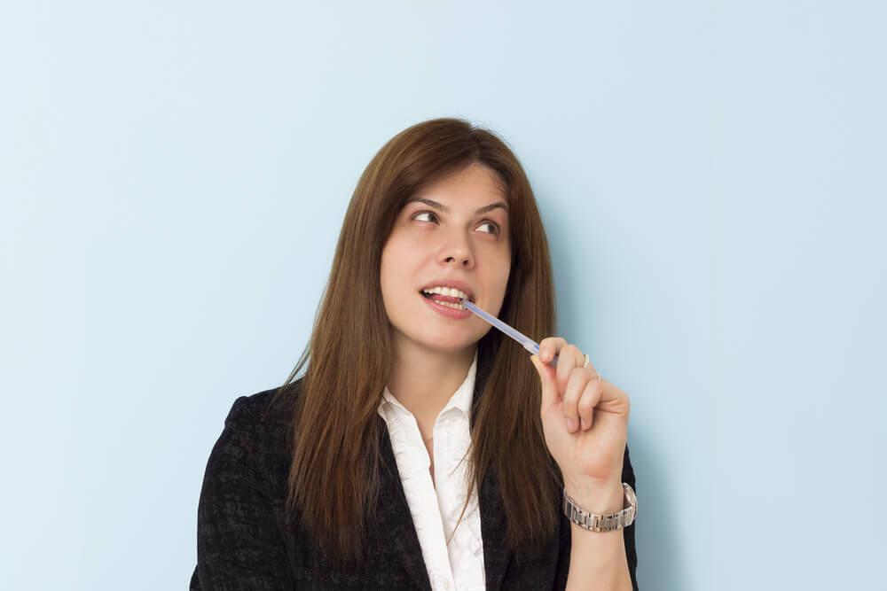 mujer mordiendo la tapa de un boli