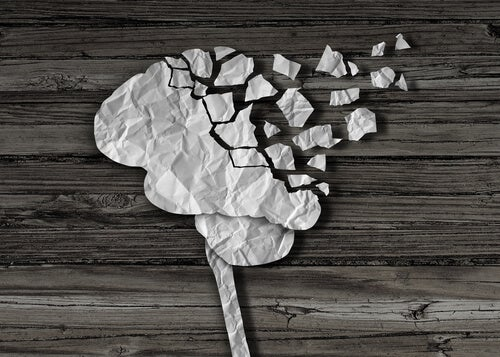 Cerebro de papel con trozos que se desvanecen