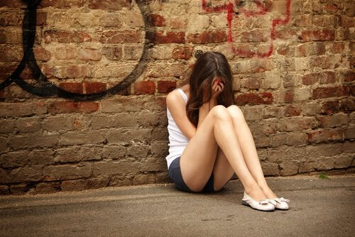 Chica adolescente con depresión sentada en el suelo